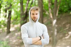 Feeling confident. Guy bearded attractive casual clothes hooded. Man with bristle confident face nature background. Defocused. Man unshaven guy looks handsome royalty free stock photo