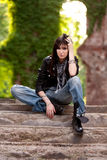 Feeling cool. Nasty brunette in leather jacket and torn jeans sitting at leisure on some stairs Stock Photography