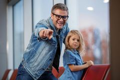 Positive middle-aged man and child are waiting for flight. Feeling curious. Cheerful mature father and his small daughter are sitting on airport seats. Parent is Stock Photo