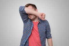 Feeling depressed. Man covering face with hand. While standing against grey background royalty free stock photo