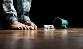 Feeling depressed. Person standing barefoot with dropped coffee cup and tissue by their feet Royalty Free Stock Image