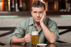 Feeling depressed. Portrait of depressed young men drinking beer Stock Photos