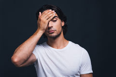 Feeling despair. Hopeless young man covering face with hand while standing against grey background Stock Image
