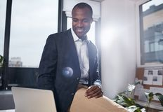 Professional positive manager is expressing gladness at work. Feeling excellent. Joyful young african businessman is sitting on table in light office and looking stock photos