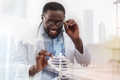 Curious doctor touching genome model. Feeling excited. Close up of young curious doctor touching genome model with the finger and showing profound interest royalty free stock photo