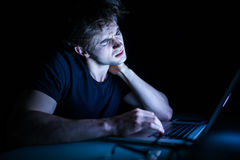 Feeling exhausted frustrated young man with neck pain while sitting in front of laptop in the night royalty free stock photo