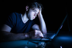 Feeling exhausted frustrated young man while sitting in front of laptop in the night Stock Photography