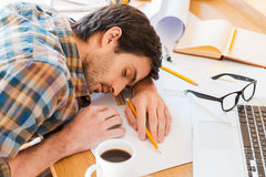 Feeling exhausted. Top view of young man sleeping while sitting at his working place Royalty Free Stock Photography