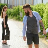 Feeling flirtatious. Bearded man and cute woman walk on street. Hipster look back at pretty woman. Couple in love on. Feeling flirtatious. Bearded men and cute stock photos