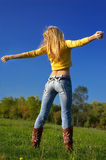 Feeling free 2. Slim shaped beautiful blond girl exercising at he meadow. slight motion blur on hands Stock Image