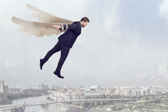 Feeling free and happy . Mixed media. Young businessman with paper wings flying in sky Royalty Free Stock Photos
