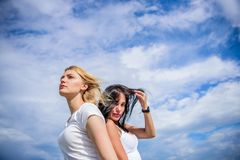 Feeling free and happy. Sexy girls on cloudy sky. Adorable women with blond and brunette hair. Pretty women with sexy stock image