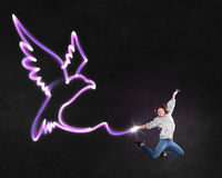 Feeling free like bird. Young girl with drawn wings jumping high in sky Stock Photography