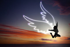 Feeling free like bird. Young girl with drawn wings jumping high in sky Royalty Free Stock Image