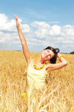 Feeling the freedom. Beautiful girl in a yellow field of wheat Stock Images
