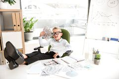 Confident stylish child is resting in office. Feeling freedom concept. Portrait of relaxed boy in glasses is holding fan of money while looking at camera with Royalty Free Stock Photos