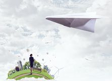 That feeling of freedom. Elegant businesswoman and big paper plane flying in sky. Mixed media Stock Image