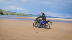 The feeling of freedom and Moto aesthetics. Motorcyclist riding on his bike on sandy beach.