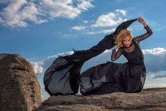 Feeling of freedom in the wind. Amazing blond in black dress enjoys the wind blowing on her hair Royalty Free Stock Photo