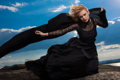 Feeling of freedom in the wind. Amazing blond with full red lips looks unforgettable in her long black dress Royalty Free Stock Photography