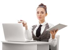 Feeling Frustrated Computer User. Young business woman sitting at table with a laptop and tablet pc, arms raised of bad news Royalty Free Stock Image