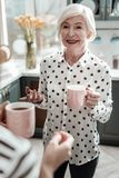 Fashionable senior woman smiling and looking happy while drinking tea stock photos