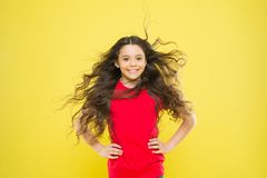 Feeling good fabulous hair. Adorable small girl smiling with long brunette hair. Happy child with flowing hair on yellow royalty free stock images