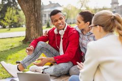 Handsome young fellow feeling good sitting near his girlfriend. Feeling good. Handsome young fellow feeling extremely good while sitting near his beautiful Royalty Free Stock Image