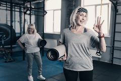 Athletic senior woman with yoga mat giving OK gesture. Feeling good. Pleasant upbeat senior women holding a yoga mat and giving an OK gesture while her friend Royalty Free Stock Photography
