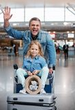 Joyful mature man and cute girl are waiting for flight. Feeling good. Portrait of cheerful middle-aged father is waving hello and pushing airport trolley with Stock Photos