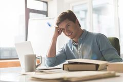 Delightful successful guy is laboring in office stock images