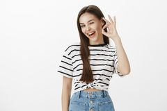 Feeling great, expressing positive mood. Studio shot of carefree confident caucasian female, winking, raising hand and. Showing okay or great sign with flirty stock images