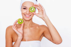 Feeling great thanks to a healthy diet. Beautiful young woman wrapped in white towel holding piece of kiwi in front of her eye while standing against white Stock Images