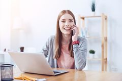 Beautiful female having friendly talk per telephone. Feeling happiness. Delighted young woman keeping smile on her face and holding smartphone near left ear Stock Image