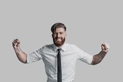 Feeling so happy!. Handsome young businessman gesturing and smiling while standing against grey background Royalty Free Stock Photography