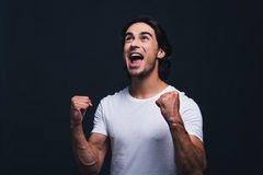 Feeling so happy. Happy young man gesturing and looking up while standing against grey background Royalty Free Stock Photo