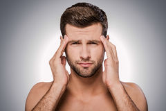 Feeling headache. Portrait of frustrated young shirtless man looking at camera and touching head with hands while standing against grey background Royalty Free Stock Photography