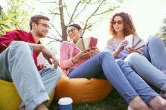 Inspired woman choosing material with her colleagues. Feeling inspired. Joyful dark-haired women sitting in the open air with her co-workers and discussing their Royalty Free Stock Image