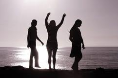 Feeling joyful. Silhouette of three girls feeling joyful at the beach stock photos