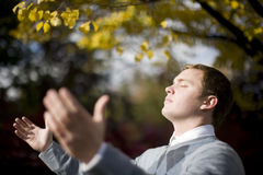 Feeling the light. Close up view of one young man with closed eyes and open arms feeling the light from the sun Stock Images