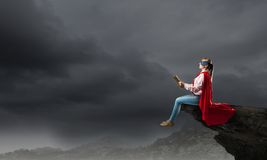 Feeling like super woman. Young woman in super hero costume reading book stock image