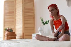 Anorexic woman with tattoos on arms feeling miserable. Feeling miserable. Red-haired anorexic woman with tattoos on arms feeling miserable while sitting on bed royalty free stock image