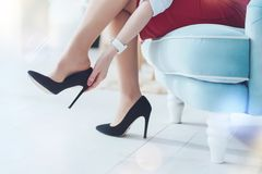Scaled up look on business woman taking off high heels stock photo