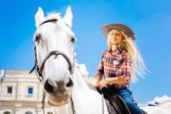 Girl with long blonde hair feeling nice while riding horse stock photos