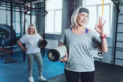 Positive senior woman gesturing ok sign at gym. Feeling ok. Selective focus on a joyful lady holding a mat and showing an ok sign while looking into the camera Stock Photo