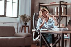 Busy businesswoman feeling overloaded with important work. Feeling overloaded. Busy appealing experienced businesswoman feeling overloaded with important work royalty free stock image