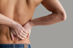 Feeling pain in back. Cropped image of young muscular man touching his back while standing isolated on grey background Royalty Free Stock Photos