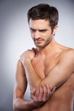 Feeling pain in elbow. Young muscular man touching his elbow and expressing negativity while standing isolated on grey background Royalty Free Stock Image