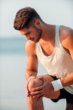 Feeling pain in his knee. Royalty Free Stock Photo