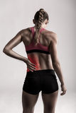 Feeling pain it my backs. Studio shot of a sporty young woman holding her lower back in pain royalty free stock photos